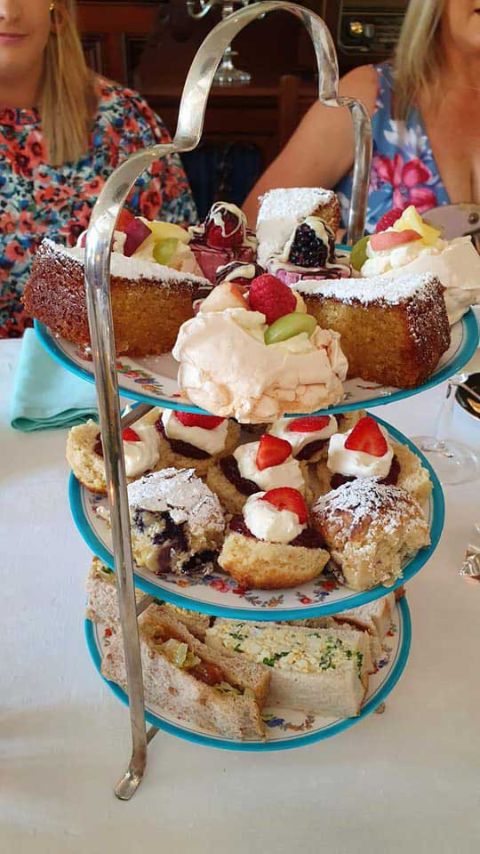 a cakestand with sandwiches and home baked goods