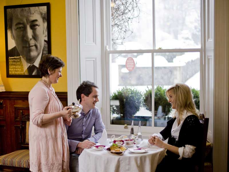 Gerardine serves visitors with tea in the dining room